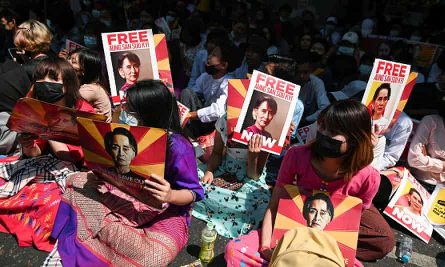 Garment workers hold placards with pictures of Aung San Suu Kyi as they rally against the military coup in Yangon, Myanmar, February 25, 2021. REUTERS/Stringer