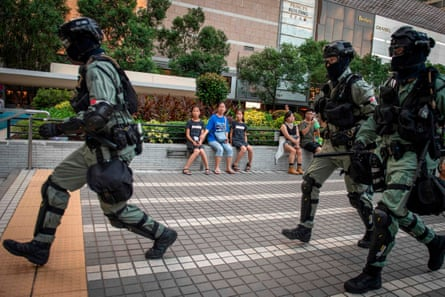 Police chase down a couple wearing facemasks (unseen) as a mom and her two daughters look on while sitting on a bench in a small park in the central district in Hong Kong