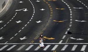 A woman walks on a crosswalk at an almost empty street on Yom Kippur in Jerusalem.