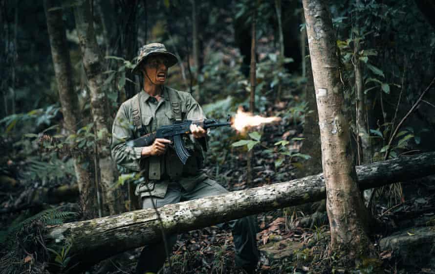 A soldier firing a machine gun in the jungle
