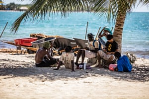 Beach cleaners take a break after shovelling sargassum seaweed off the sand at Placencia in southern Belize.