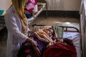 A midwife checks on exhausted new mother Hazera Begum, 18, who is recuperating next to her daughter, three-day-old Kismat Ara, at the Unicef-supported birthing centre in the Kutupalong camp for Rohingya refugees, in Cox's Bazar, Bangladesh