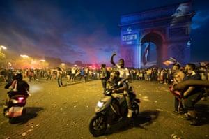 Supporters celebrate near the illuminated Arc de Triomphe in Paris