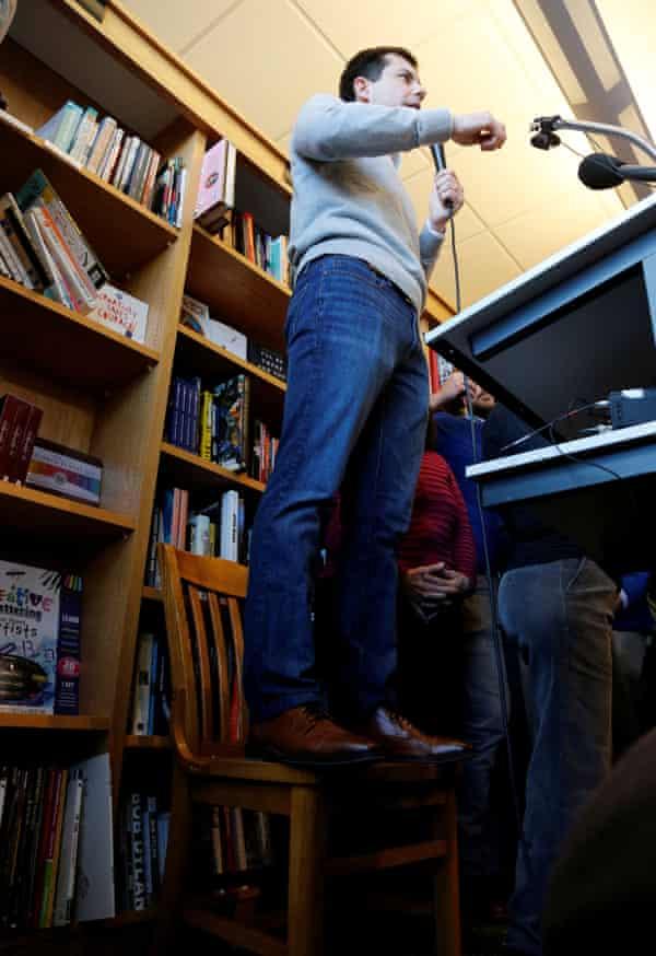 Pete Buttigieg stands on a chair.