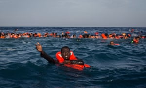 Refugees shout for help after a boat capsized off Italy last year.
