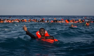 A migrant calls for help after a boat carrying more than 500 people capsized off Lampedusa, Italy, in May 2017.