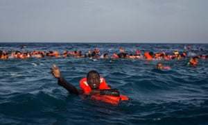 Refugees and migrants are seen swimming and yelling for assistance from crew members from the Migrant Offshore Aid Station (MOAS) 'Phoenix' vessel after a wooden boat bound for Italy carrying more than 500 people capsized on May 24, 2017 off Lampedusa, Italy