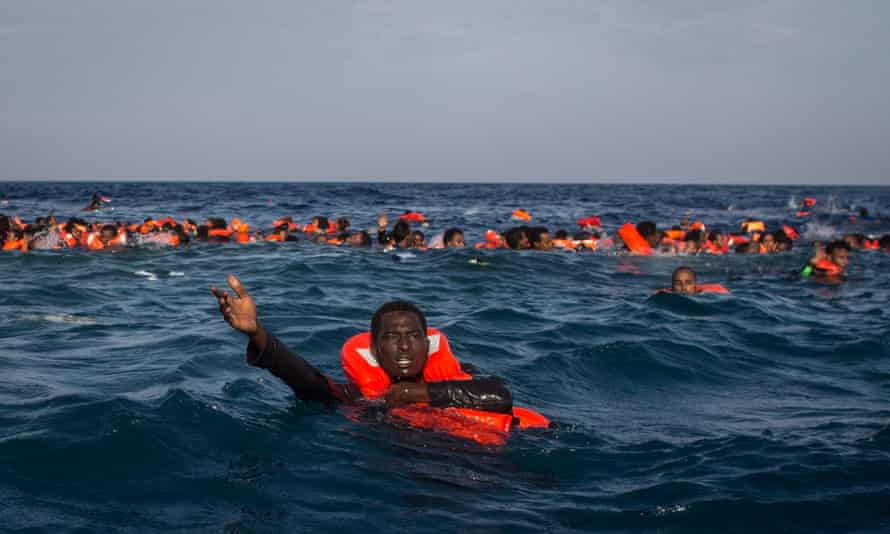 Refugees and migrants yell for help after their wooden boat capsizes off Lampedusa, Italy.