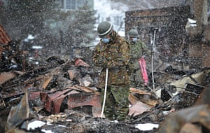 A member of the Japanese self-defence forces offers a prayer before removing the body of a tsunami victim found buried in the rubble.