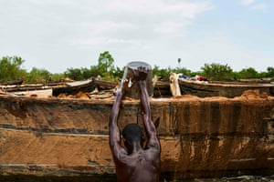 A digger loads his boat with sand collected from the Niger River. The men are paid around $16 to $23 for three days of work