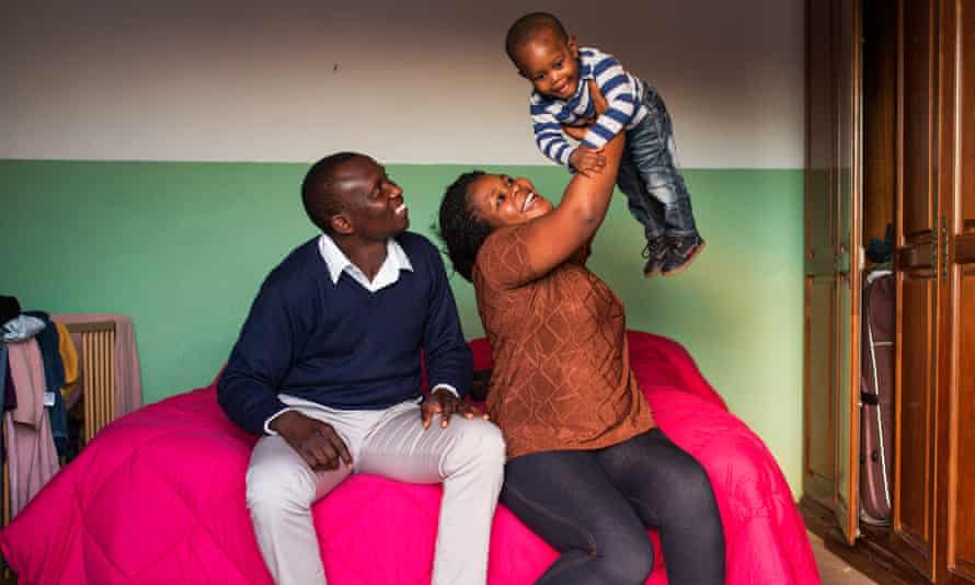 Nigerian John Babalola Wale at home with his wife and son in Sutera. They and other African migrants are helping to repopulate the village.