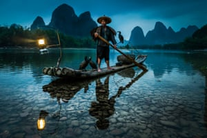 A Guilin cormorant fisherman sets out on the river Li during the blue hour