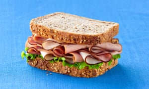 Meat and lettuce sandwich against blue background