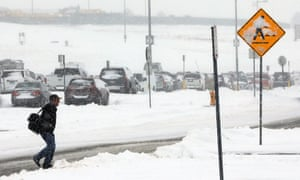 A traveler makes his way to a shuttle stop after a snowstorm at Denver international airport.