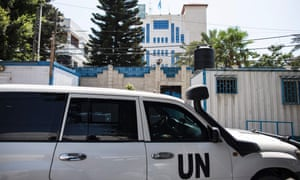 United Nations Development Programme staff drive an official car in front of its headquarters in Gaza