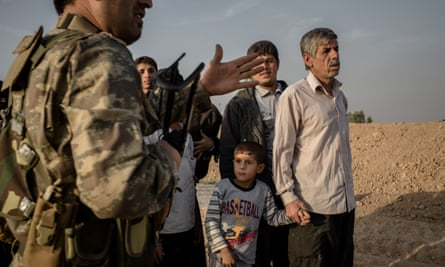 A Peshmerga fighter directs displaced citizens at a camp near Khnash, Iraq.