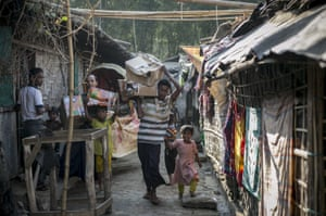 A family carries boxes of supplies through the Leda refugee camp