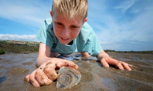 A boy with an ammonite fossil on the Beach at Robin Hood's Bay, part of the Yorkshire Jurassic coast.