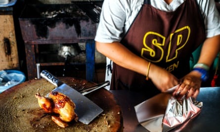 A young chef prepares roast chicken at SP Chicken restaurant in Chiang Mai, Thailand.