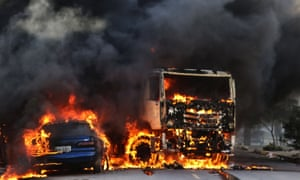 Vehicles burn in the street after attacks in the city of Fortaleza