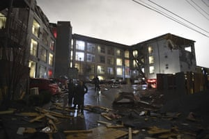 As the sky lightens, debris is scattered across the parking lot of a damaged apartment building.