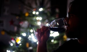 A man drinks a glass of wine by a Christmas tree.