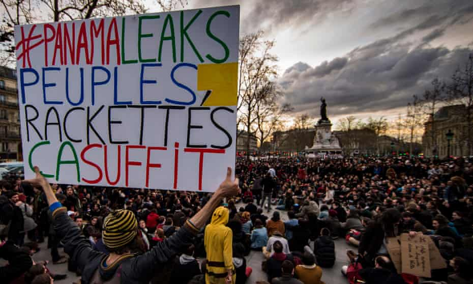 A protester holds a sign which reads '#Panama leaks, racketeered people, that's enough' in Paris.