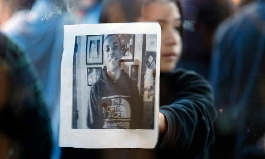 A child holds up a picture of Stephon Clark during a protest outside the NBA game between the visiting Atlanta Hawks and Sacramento Kings in Sacramento, on 22 March.