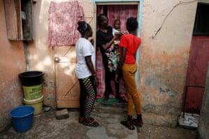 Khadjou Sambe, 25, Senegal's first female professional surfer, talks to Diadou Ndiaye, as a young surfer stands by, in Ngor, Dakar, Senegal, July 30, 2020