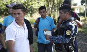Honduran migrants trying to reach the US show their ID card to a Guatemalan national police agent in Morales, Guatemala, 15 January 2020.