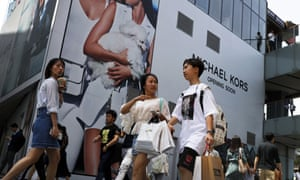 Chinese shoppers walk through a mall in Beijing.