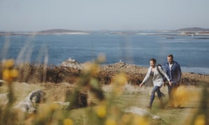 couple walking by sea in scilly isles