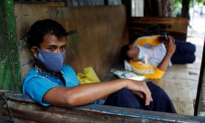 School bus driver Yusuf Iswahyu rests before transporting infected patients to an emergency hospital
