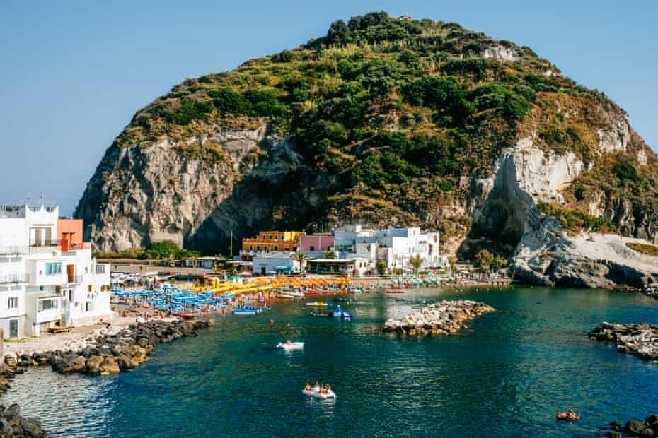 A crowded beach on the island of Ischia, Italy, between a large rock formation and a small town.
