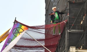 An Extinction Rebellion protester who has scaled the scaffolding surrounding Big Ben, wearing what seems to be a Boris Johnson wig.