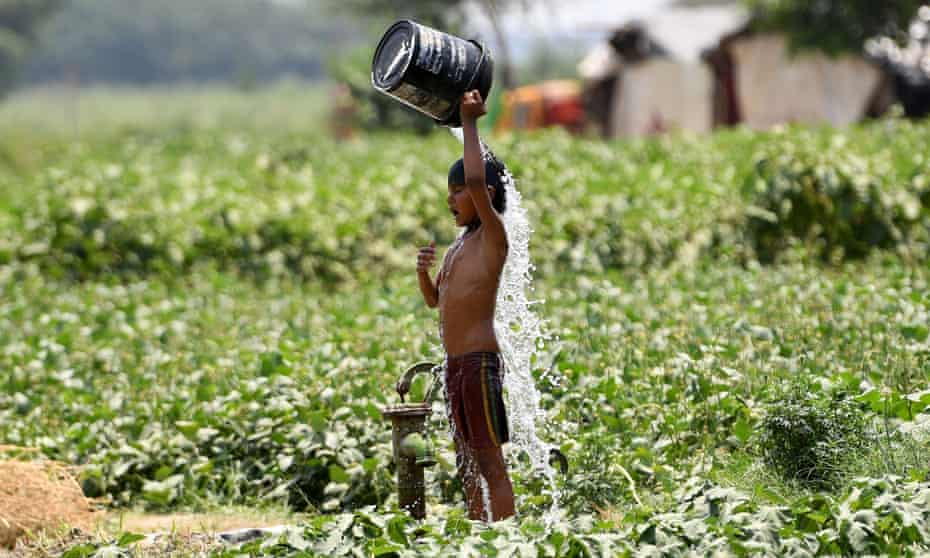A boy tips a bucket of water over himself in Delhi, India
