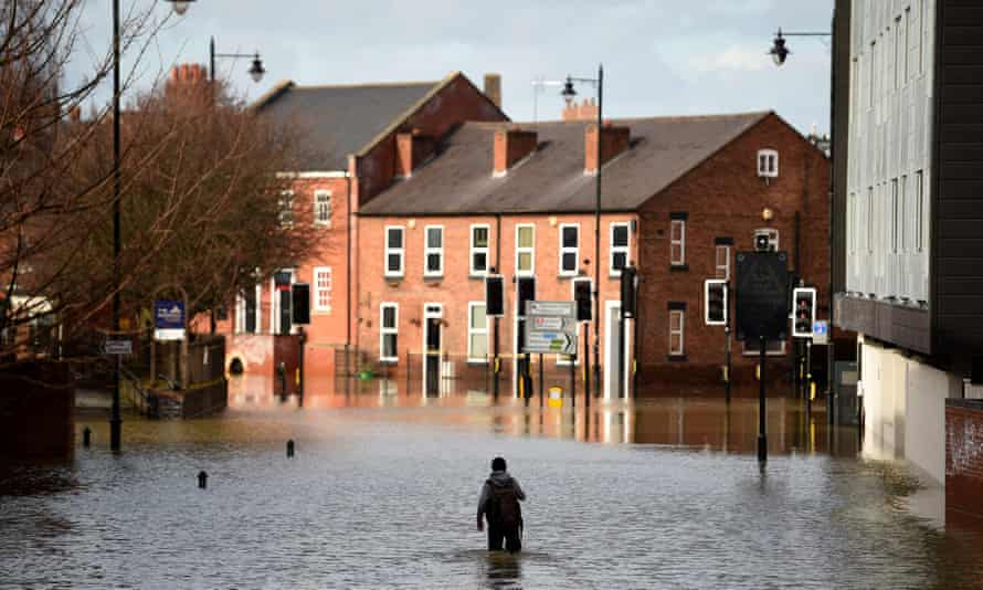 A man wades through flood waters in Shrewsbury.