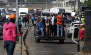 People in the city of Maracaibo in Venezuela ride in the back of a pickup truck to make up for a lack of public transport.