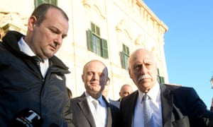 Malta's prime minister, Joseph Muscat, centre, is shielded by bodyguards after leaving a cabinet meeting on 26 November.