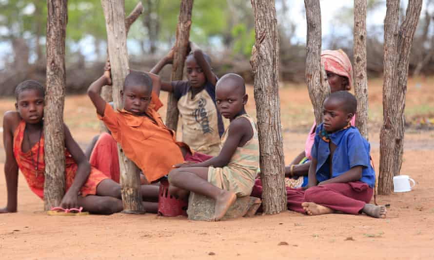 Children in Mafomoti village, in Zimbabwe's Mwenezi district, wait while their mothers prepare their first and only meal of the day