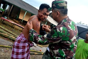 A soldier examines as he takes care of a local resident who was injured following a tsunami which hit at Tanjung Lesung district in Pandeglang, Banten province, Indonesia