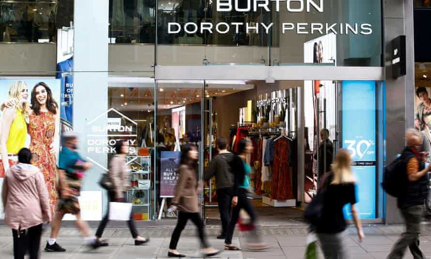 People walk past a Burton and Dorothy Perkins shop in central London