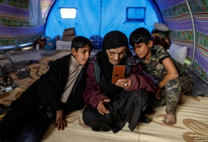 Khatla Ali Abdullah, 90, who recently fled her home in al-Mamoun district, looks at photographs on a mobile phone as she sits with her grandsons in her tent in Hammam al-Alil camp in western Mosul, Iraq, on 1 March