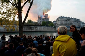 Bystanders look on as flames and smoke billow from the roof at Notre Dame Cathedral in Paris.