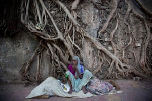 A woman sits in front of the dried roots of a banyan tree in Mumbai