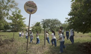 Children walk past a sign warning of the danger of hippos near the Hacienda Napoles.