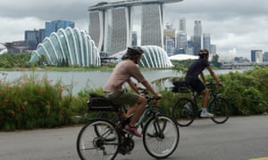 Cyclists ride along Marina Bay overlooking the financial business district in Singapore on July 14, 2020