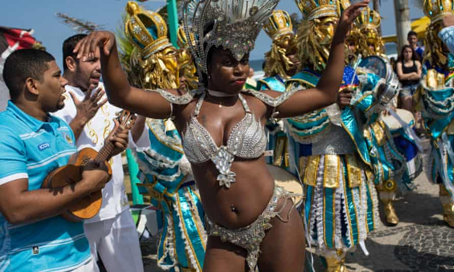 A samba dance group perform on the street while waiting for the arrival of the Olympic torch in Rio de Janeiro.