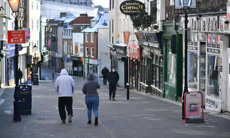 Pedestrians walk along a high street with the shops closed in Maidstone, southeast England as life continues in Britain's third coronavirus lockdown that has closed all non-essential stores in an effort to suppress Covid-19 infections.