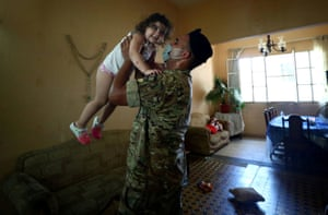 A soldier greets Christy Faraj Oghlo, 2, after delivering a food parcel to her grandmother Souzy Bedigian's home, where Christy, her brother and their parents are staying, after an explosion on the Beirut port damaged their home, in Beirut, 16 August